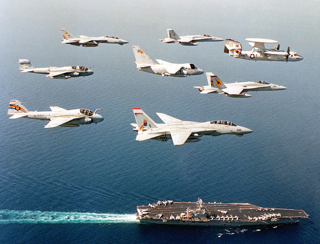 Aircraft from the USS Carl Vinson fly in formation above their carrier in the Persian Gulf during a deployment.