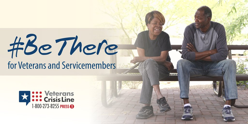 Two veterans, a man and woman, talking with each other on a park bench.
